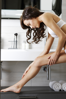 Beautiful young woman moisturising her legs in bathroom.